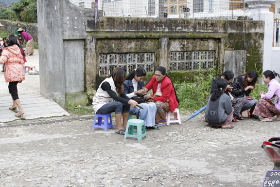 Gem dealers sit on stools at the side of a street in Kyatpyin, during a sesseion of hta-pwe.