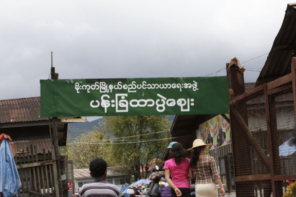 "The signboard as seen from the other hta pwè, just across the street. The signboard says, ""Mogok Township Municipal Board"", "" Panchan Hta-pwè Bazaar (or Market)"""