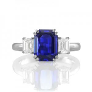 A blue emerald cut sapphire ring